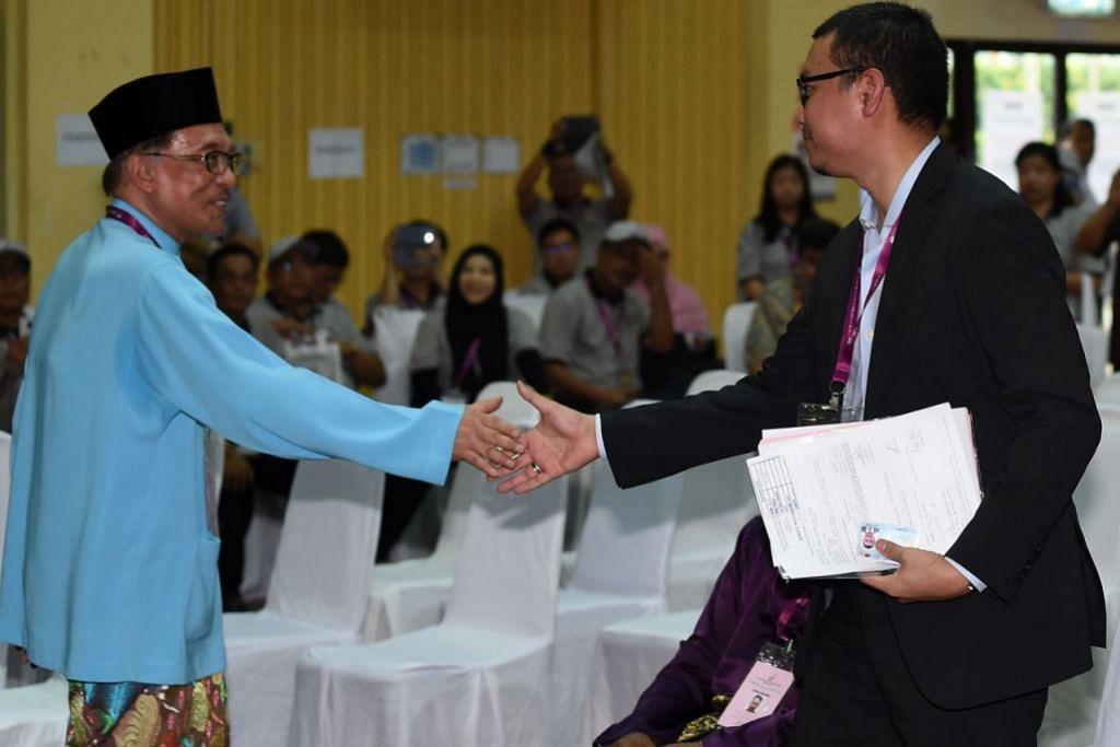 BERTENTANG MATA: Datuk Seri Anwar (kiri) bersalaman dengan bekas pembantu peribadinya, Encik Saiful Bukhari, seorang calon Bebas, yang pernah mendakwanya atas tuduhan sodomi pada 2008. – Foto AFP