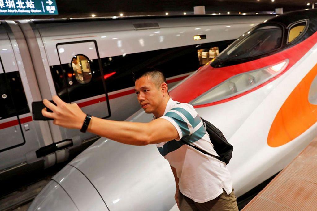 MUDAHKAN PERJALANAN: Penumpang ini sempat 'berselfie' dengan kereta api berkelajuan laju yang menghubungkan Hongkong dengan China dan mula beroperasi pada 23 September lalu. - Foto REUTERS