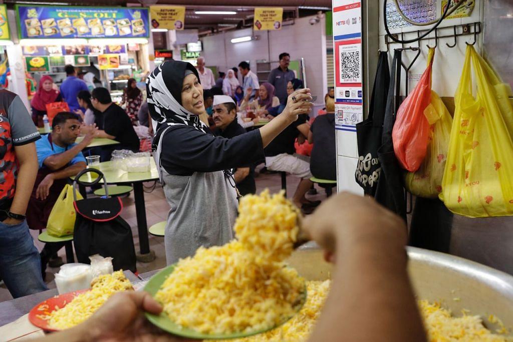 AMBIL PELUANG MANFAATKAN TEKNOLOGI: Cik Hamidah Abdul Kadir, 51 tahun, seorang suri rumah, mencuba pembayaran kod QR Nets di Gerai Briyani Geylang di Pasar dan Pusat Makanan Geylang Serai.  - Foto BH oleh KEVIN LIM