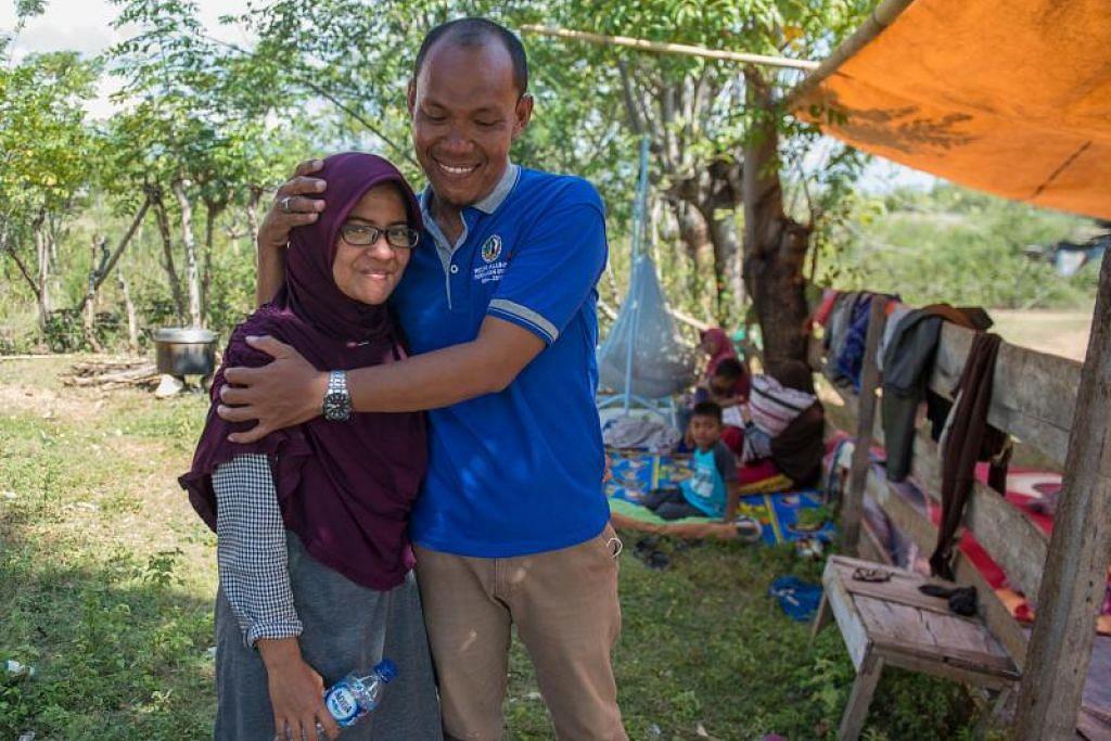 Azwan memeluk isterinya Dewi Prasasti selepas menjumpai Dewi yang berada dalam keadaan selamat dan sihat selepas dihanyutkan ombak tsunami yang melanda bandar Palu, Indonesia. - Foto AFP