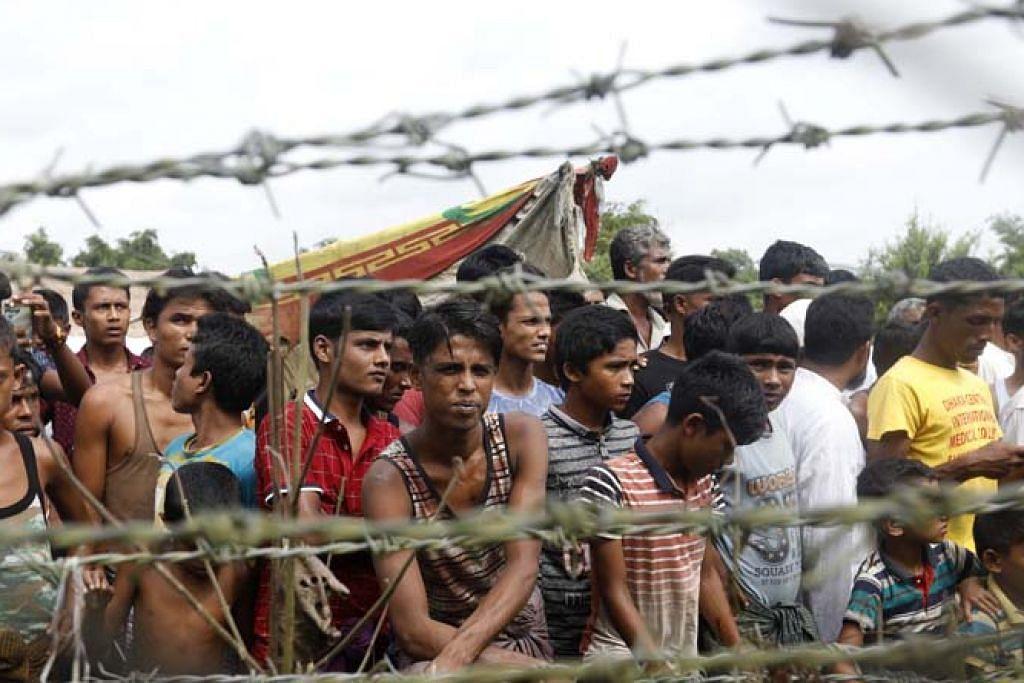 NASIB MALANG: Sekumpulan pelarian Rohingya berkumpul di belakang pagar berduri di sempadan Bangladesh-Myanmar. Menteri Luar Asean baru-baru ini melahirkan keprihatinan mendalam mengenai dakwaan tindakan keganasan yang berlaku ke atas kaum Rohingya. - Foto EPA