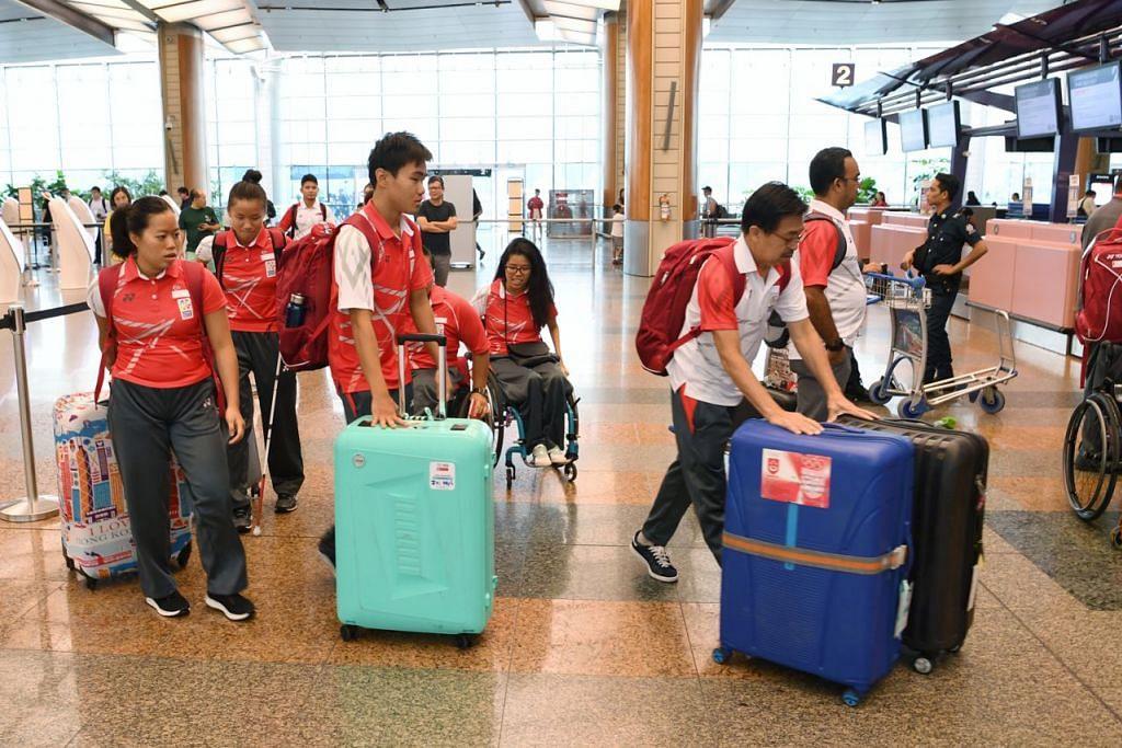 SEMBANGAT BERKOBAR: Atlit para negara berkumpul di Lapangan Terbang Changi dan bersiap sedia untuk berangkat ke Jakarta. - Foto BH oleh KHALID BABA