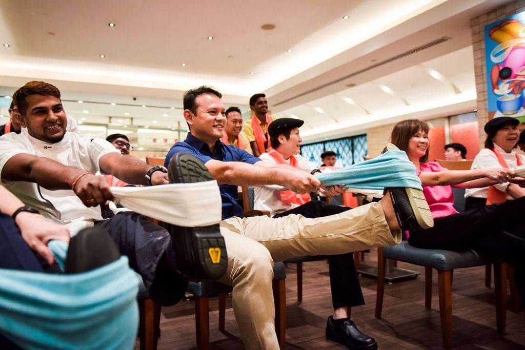 SENAM BERSAMA: Encik Zaqy Mohamad (dua dari kiri) dan Dr Amy Khor (dua dari kanan) menyertai sekumpulan pekerja di restoran Carousel di Hotel Royal Plaza on Scotts melakukan senaman bersama semalam. - Foto-foto BH oleh MATTHIAS CHONG