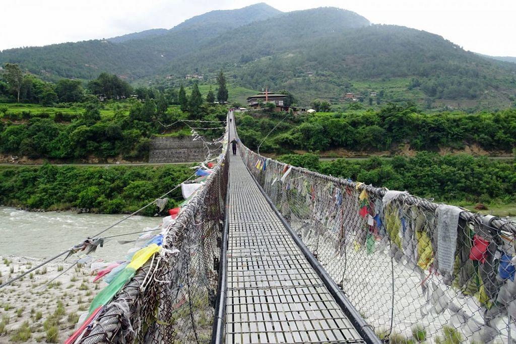 LAWAN PERASAAN NGERI: Penulis orang terakhir dalam rombongan yang menyeberangi sungai dengan berjalan di jembatan tergantung terpanjang di Bhutan.  - Foto JAMSARI AHMAD
