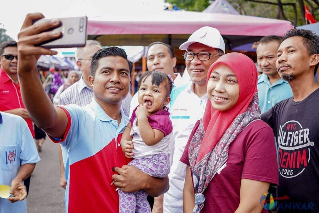 BERAMAH MESRA: Datuk Anwar (tengah dan bertopi) sempat menyapa para pengundi semasa mengunjungi peniaga Pasar Tani Batu 4, Bagan Pinang, Port Dickson, pagi semalam. - Foto TWITTER ANWAR IBRAHIM