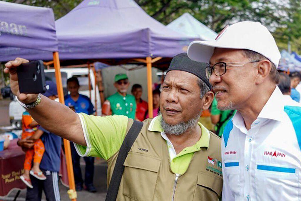 BERGAMBAR SAMA: Seorang penduduk di Port Dickson sempat 'berselfie' dengan Datuk Seri Anwar (kanan) yang kini gigih berkempen menjelang pilihan raya kecil di kawasan itu. - Foto TWITTER