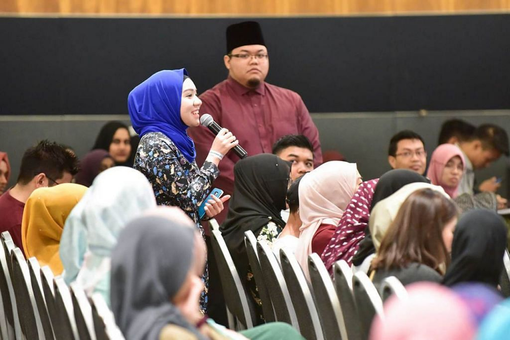 PERBINCANGAN RANCAK: Seorang peserta (memegang mikrofon) mengajukan soalan di rahat separuh hari itu. Memerhatikan beliau ialah Ustaz Muhammad Azim Mohamed Foad yang turut menjayakan rahat itu. - Foto MUIS