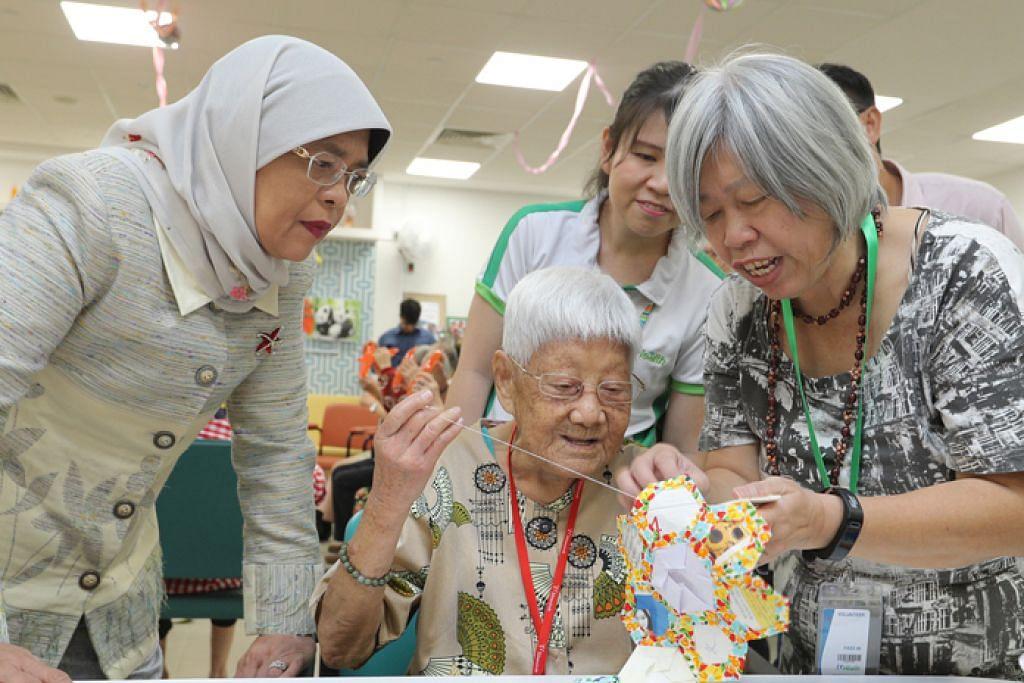 TEKUN TELITI: Puan Halimah menyaksikan penduduk, Cik Leong Hup Sow, yang masih lagi mahir dan teliti melakukan kerja tampal cantum (patchwork) walaupun beliau sudah berusia 91 tahun semasa lawatannya ke Kampung Admiralty semalam. - Foto MCI