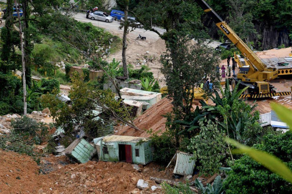 Tanah runtuh di tapak binaan Jalan Bukit Kukus. Ia menimbus empat kontainer yang didiami pekerja asing. Foto: BERNAMA