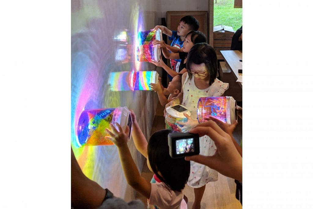 TERPESONA DENGAN HASIL LUKISAN: Kanak-kanak menunjukkan hasil lukisan bekas biskut PET mereka yang akan dipamerkan sebagai pemasangan seni lampu, The Rainbow Connection, di 'i Light Singapore - Bicentennial Edition' tahun depan. - Foto BH oleh ZULAIQAH ABDUL RAHIM
