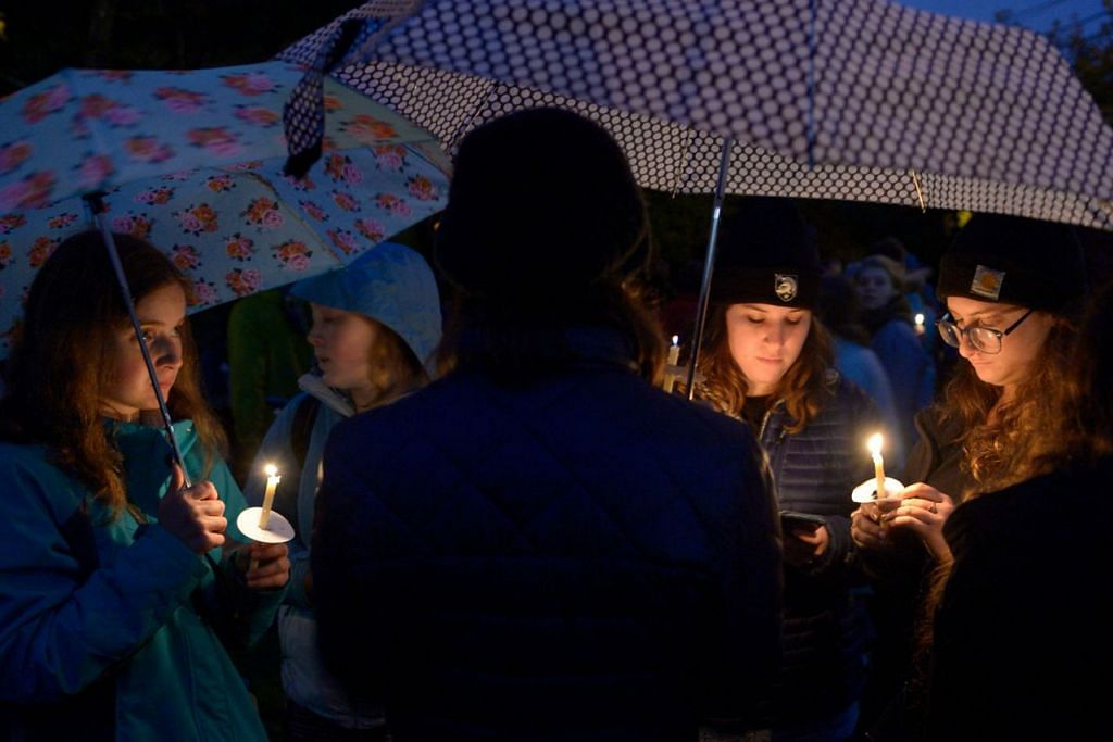 MEMPERINGATI MANGSA: Para penduduk di kejiranan Squirrel Hill, Pittsburgh, (kiri) berkumpul dan menyalakan lilin bagi memperingati mangsa. - Foto AFP