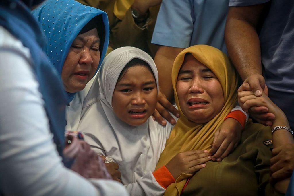 SEBAK: Beberapa anggota keluarga penumpang pesawat Lion Air JT 610 yang terhempas tidak dapat menahan rasa sedih di lapangan terbang Pangkal Pinang, Bangka Belitung, semalam. - Foto AFP