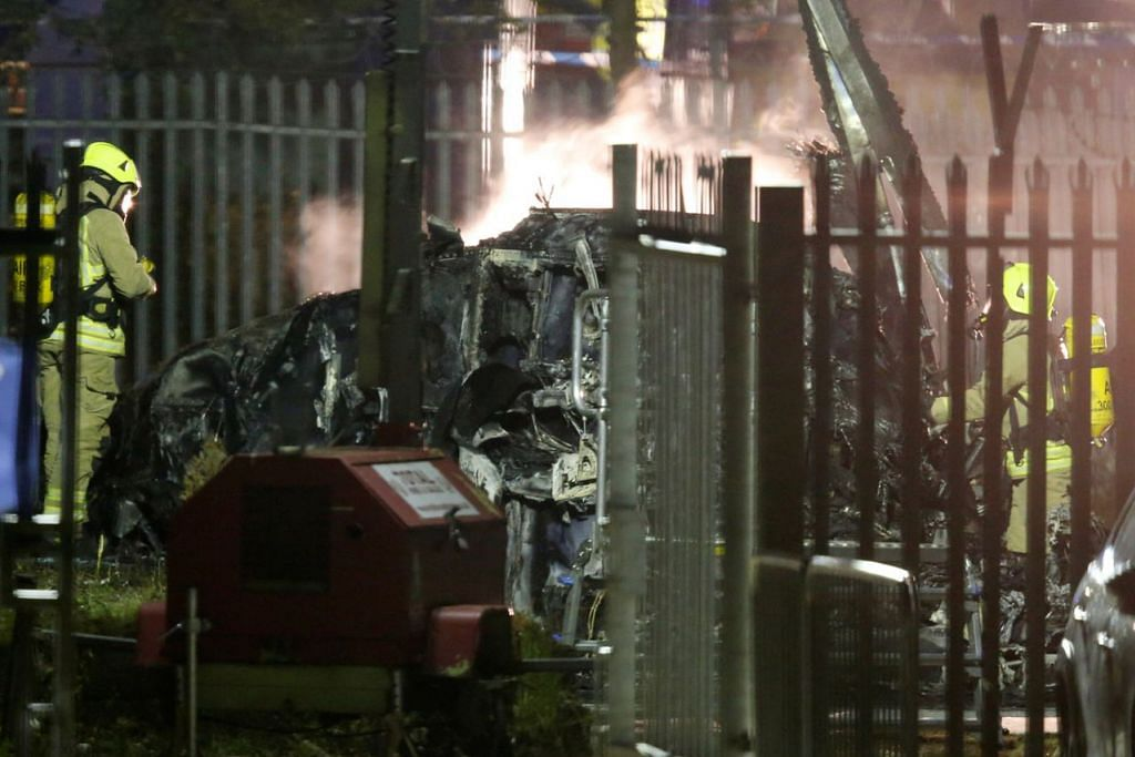 NAHAS: Pegawai bomba memeriksa bangkai helikopter dinaiki Encik Vichai Srivaddhanaprabha yang terhempas di luar Stadium King Power, Leicester City, Sabtu lalu.  - Foto REUTERS