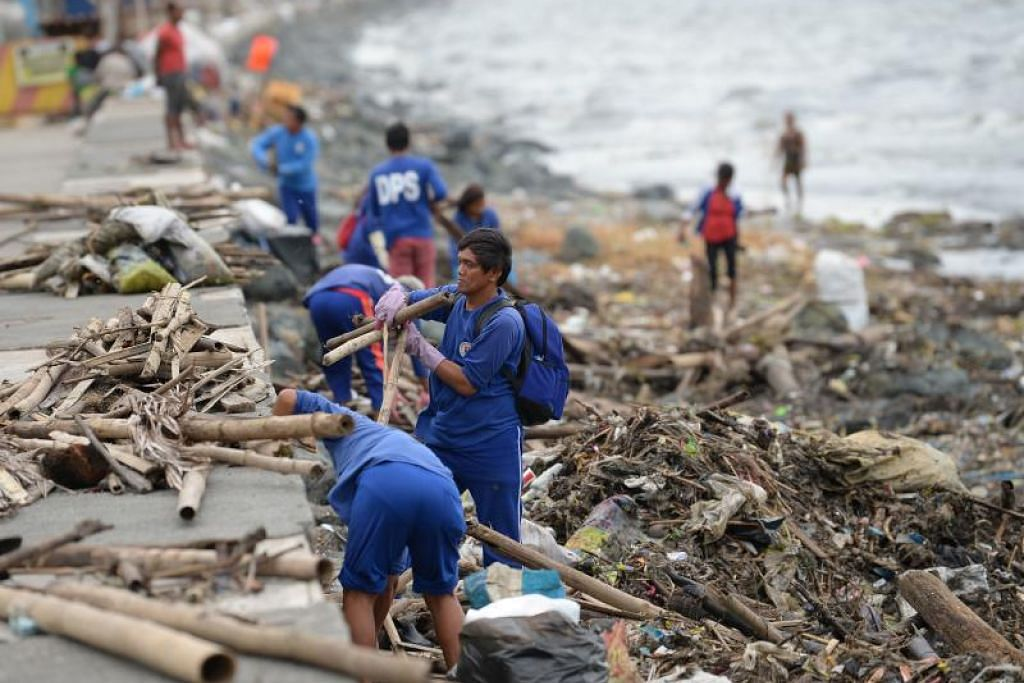 Pekerja mengalihkan serpihan yang terdampar di tepi laut di Manila pada 30 Oktober selepas Taufan Yutu melanda. Foto: AFP