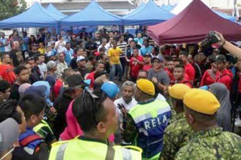 PERANG MULUT: Penyokong Datuk Seri Azmin Ali dan Encik Rafizi Ramli terlibat dalam perang mulut yang mengakibatkan anggota keselamatan Rela melangkah masuk untuk meleraikan mereka di Dewan Majlis Perbandaran Ampang di Taman Chempaka semasa pemilihan PKR di Selangor hujung minggu lalu. - Foto THE STAR