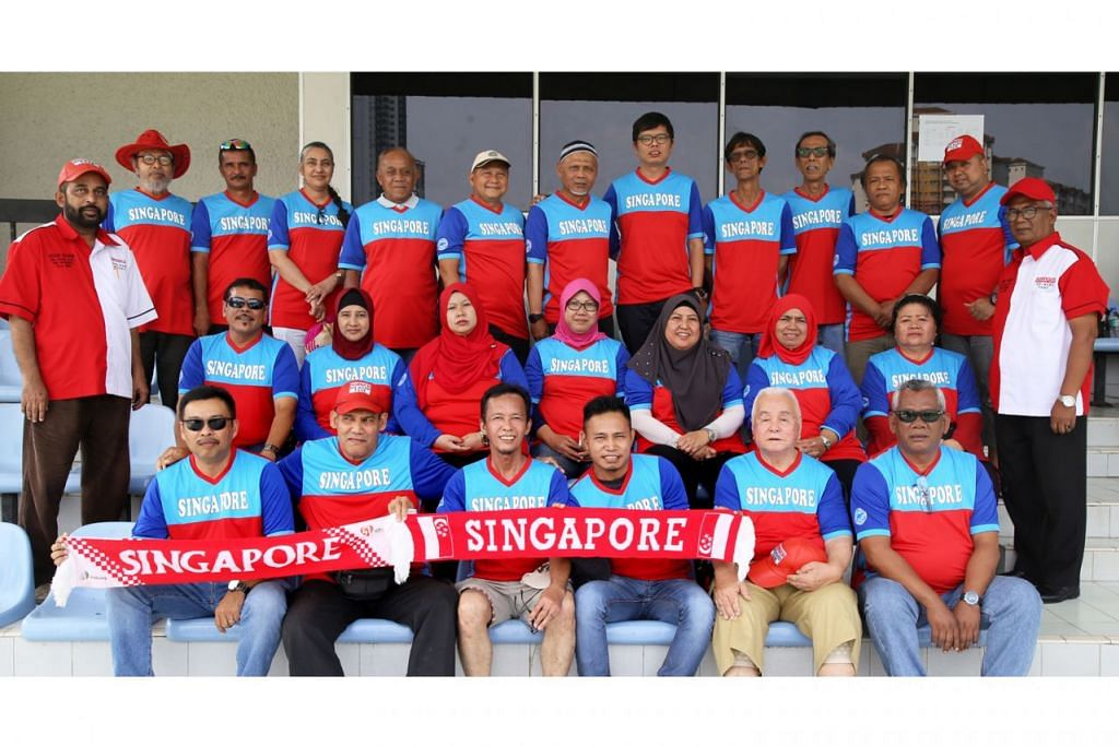 SOKONGAN PADU: Encik Akbar Hashim (kiri, bertopi dan berbaju merah putih) bergambar bersama anggota kelab penyokong Die Hard Fans Singapura semasa melancarkan jersi yang akan mereka gunakan bagi perlawanan Piala AFF Suzuki kali ini. - Foto SHAFIE GOH