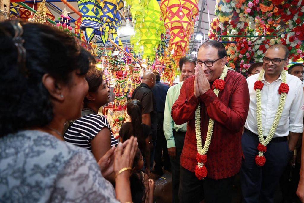 SIFAT MEMBERI DALAM SAMBUTAN DEEPAVALI: Encik S. Iswaran (berbaju merah) yang diiringi Menteri Negara Kanan (Pengangkutan merangkap Perhubungan dan Penerangan) Dr Janil Puthucheary (berbaju putih) semasa kunjungan di bazar perayaan di Little India, menderma kepada Project Give oleh Sinda pada 1 November lalu bagi pihak Pusat Masyarakat West Coast (WC) dan Jawatankuasa Eksekutif Kegiatan India WC. - Foto BH oleh TIMOTHY DAVID
