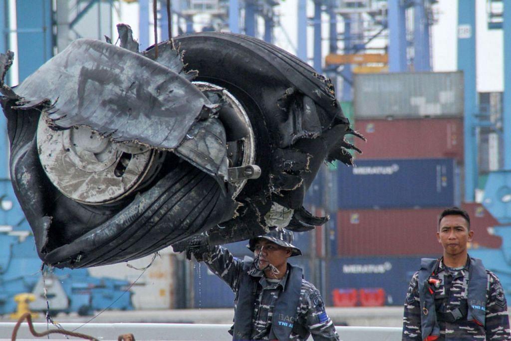 JUMPA RODA: Anggota pasukan penyelamat Indonesia semalam memindahkan roda pesawat Lion Air di pelabuhan Tanjong Priok di Jakarta. Roda itu dijumpai di laut. - Foto AFP