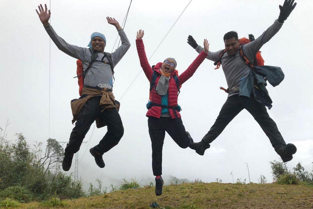 LOMPAT KEGEMBIRAAN: Para peserta ETF Climbathon (dari kiri) Encik Muhammad Nazri Khalid, Cik Natasha Mohd Satar dan Encik Abdul Mateen Affandi sempat bergambar semasa pendakian berlatar belakangkan kabus yang menyelubungi gunung-ganang di persekitaran Gunung Fansipan. - Foto SHAFIRA ZAILANI