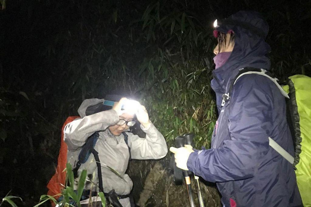 MENDAKI DALAM GELAP MALAM: Dalam keadaan gelap-gelita, peserta hanya bertemankan lampu suluh dan bulan purnama semasa pendakian malam di Gunung Fansipan. - Foto SHAFIRA ZAILANI