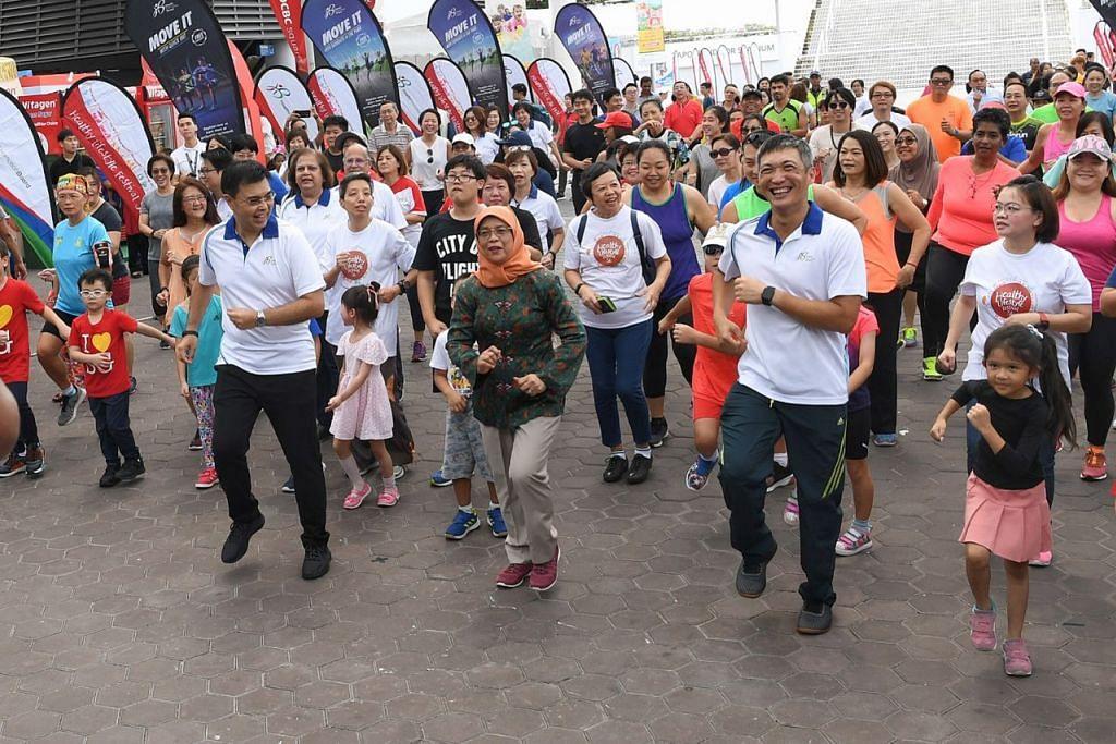GALAK GAYA HIDUP SIHAT: Presiden Halimah Yacob (tengah berbaju hijau) menyertai orang ramai melakukan The Greater Singapore Workout di Hab Sukan ,Singapura semalam. Bersama-sama beliau ialah CEO HPB, Encik Zee Yoong Kang (dua dari kanan) dan Pengerusi HPB, Encik Philip Lim (empat dari kanan).- Foto BH oleh KHALID BABA