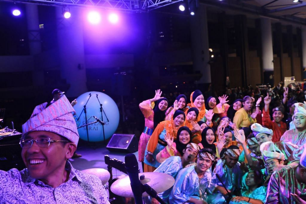 BERGAMBAR BERSAMA: Dr Maliki Osman (kiri) yang 'berselfie' dengan kumpulan dikir barat di atas pentas, turut menyertai persembahan kumpulan itu dalam satu segmen pesta Gala-Laga di WGS kelmarin. - Foto WGS