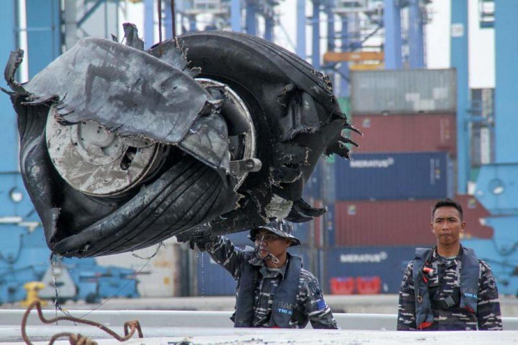 Anggota pasukan penyelamat Indonesia mengangkat tayar pesawat Lion Air yang ditemui. Foto: AFP