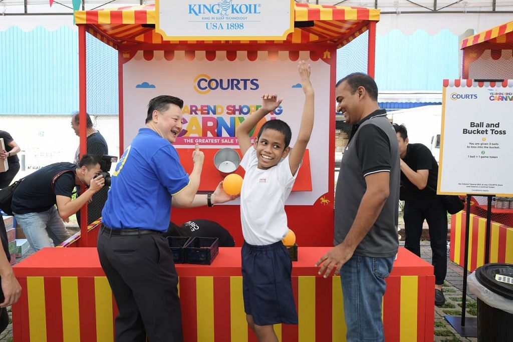 SERONOK: Antara kanak-kanak dari pertubuhan khidmat sosial AWWA yang bermain di reruai permainan di Karnival Mega Courts ialah Muhammad Rezky Adrian, 12 tahun. Turut bersamanya ialah Ketua Pegawai Eksekutif Courts, Encik Ben Tan (kiri) dan Pemangku Ketua Pegawai Eksekutif AWWA, Encik Karthikeyan J R (kanan). - Foto BH oleh ALPHONSUS CHERN