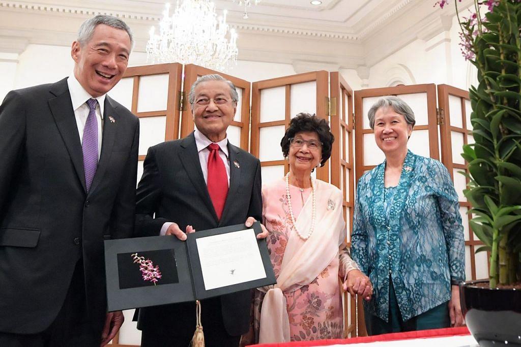 DIPLOMASI ANGGERIK: (Dari kiri) Encik Lee, Dr Mahathir bersama isterinya, Datin Siti Hasmah dan isteri Encik Lee, Cik Lee, bergambar dengan anggerik Dendrobium Mahathir Siti Hasmah yang dinamakan sempena pasangan itu di Istana semalam. - Foto BH oleh ALPHONSUS CHERN