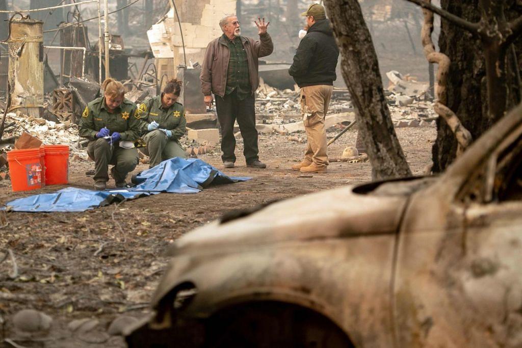 KORBAN 'CAMP FIRE': Seorang pemandu kereta mayat (tengah) bercakap tentang jumlah mayat, sedang pegawai Syerif Fresno County menguruskan mayat yang ditemui di Paradise, utara California. – Foto AFP