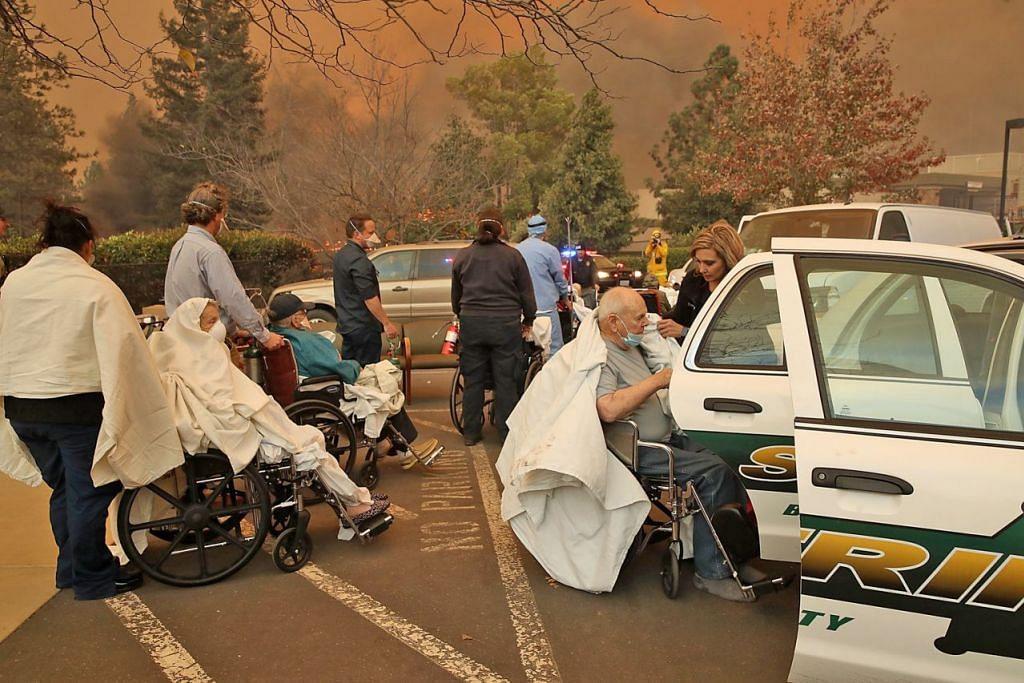 SELAMATKAN PESAKIT: Kakitangan dan sukarelawan memindahkan pesakit dari Hospital Feather River sedang api 'Camp Fire' merebak mengganas di Paradise, utara California. – Foto AFP