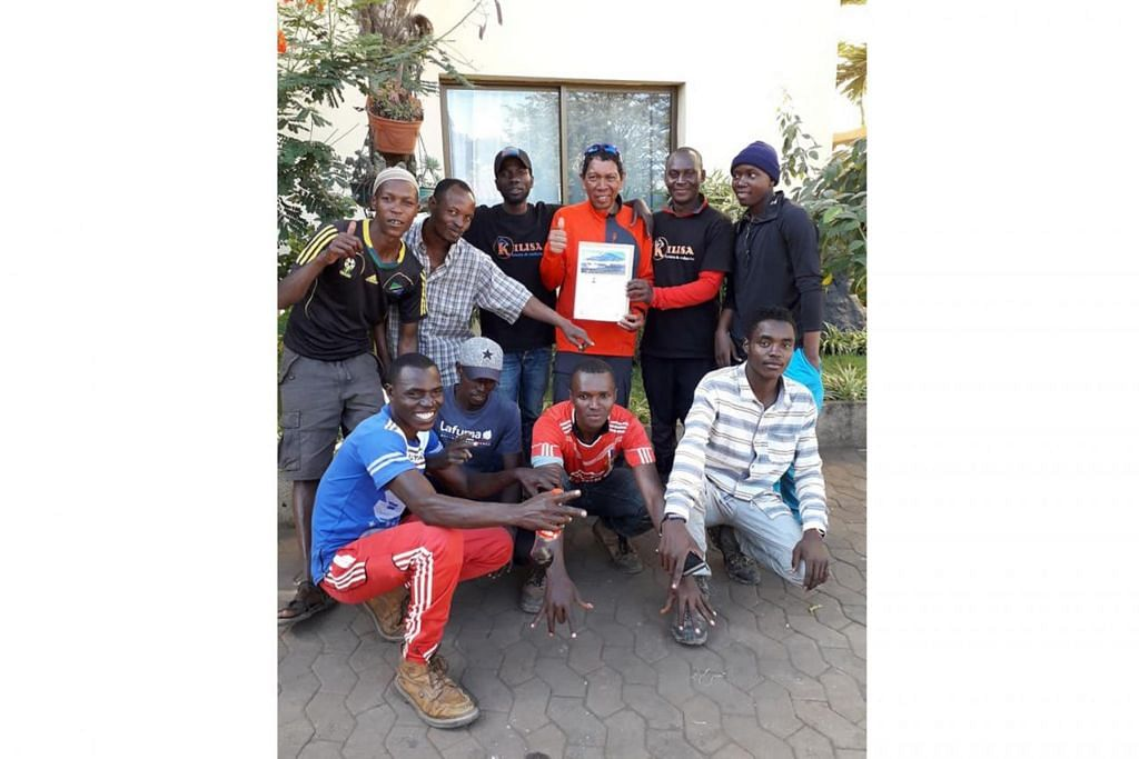 KERJA SEPASUKAN: Penulis (berdiri, tiga dari kanan) meraikan kejayaan bersama Team Kilisa, yang terdiri daripada jurupandu, tukang masak dan tujuh 'porter'. – Foto  ihsan MOHAMMAD RAFIE SABARSHAH
