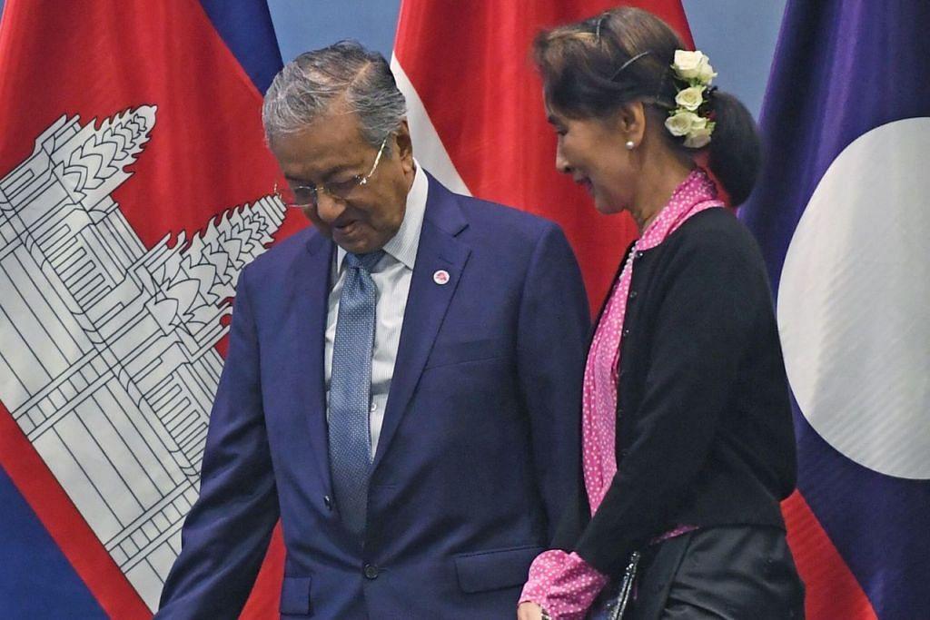 DIPERSILAKAN: Pemimpin Myanmar, Cik Aung San Suu Kyi dan Perdana Menteri Malaysia Tun Dr Mahathir Mohamad, meninggalkan pentas sebelum jamuan tengah hari pada Rabu lalu sempena sidang puncak Asean. - Foto AFP