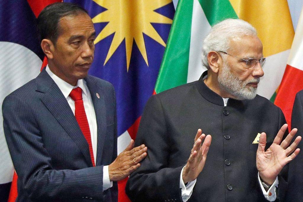 PEMIMPIN DUA NEGARA BESAR: Presiden Indonesia Joko Widodo menyapa Perdana Menteri India Narendra Modi semasa mereka bergambar pada sidang Puncak Perjanjian Kerjasama Ekonomi Menyeluruh Serantau (RCEP). - Foto REUTERS