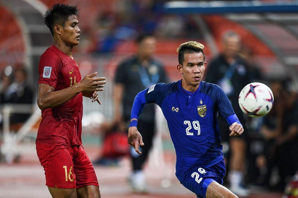 TIADA MASALAH: Pemain Thailand Sanrawat Dechmitr (kanan) sedang merebut bola dengan pemain Indonesia, Fachrudin Aryanto, dalam pertandingan yang menyaksikan Thailand mengatasi Indonesia 4-2 di padang sendiri pada Sabtu lalu.  - Foto AFP
