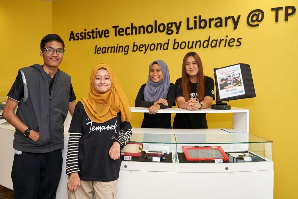 BENTUK RUANG INKLUSIF: Pelajar istimewa di Politeknik Temasek (dari kiri) Encik Danial Asri dan Cik Nur Sabrina Suhaimi mampu meninjau alat canggih yang membantu mengenal pasti suara, menyalin nota menggunakan sistem Braille dan membesarkan saiz teks di Perpustakaan Teknologi Bantuan @ TP. Bersama mereka ialah pelajar Diploma Pengajian Psikologi (dari kanan) Cik Athira Maswan dan Cik Nurul Nadia Yeo, yang teruja ingin menyumbang ke arah peningkatan pendidikan buat pelajar istimewa. - Foto POLITEKNIK TEMASEK