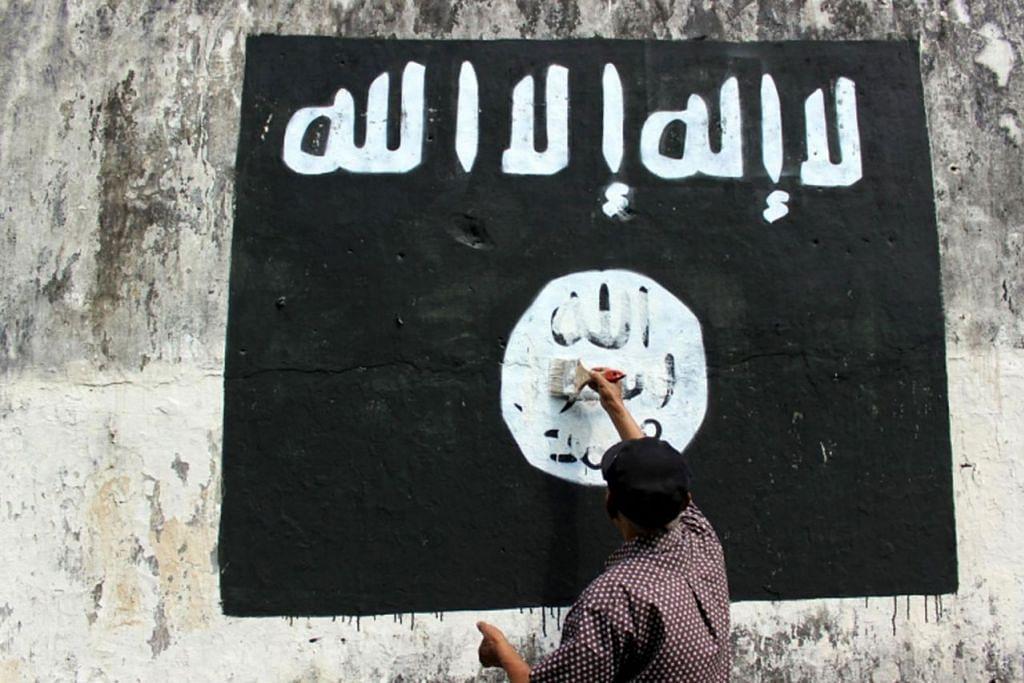 TOLAK KEHADIRAN ISIS: Seorang penduduk di Jawa Tengah mengecat bagi memadamkan bendera IS yang dilukis penyokong tegar kumpulan militan tersebut di bandar itu. - Foto TEMPO