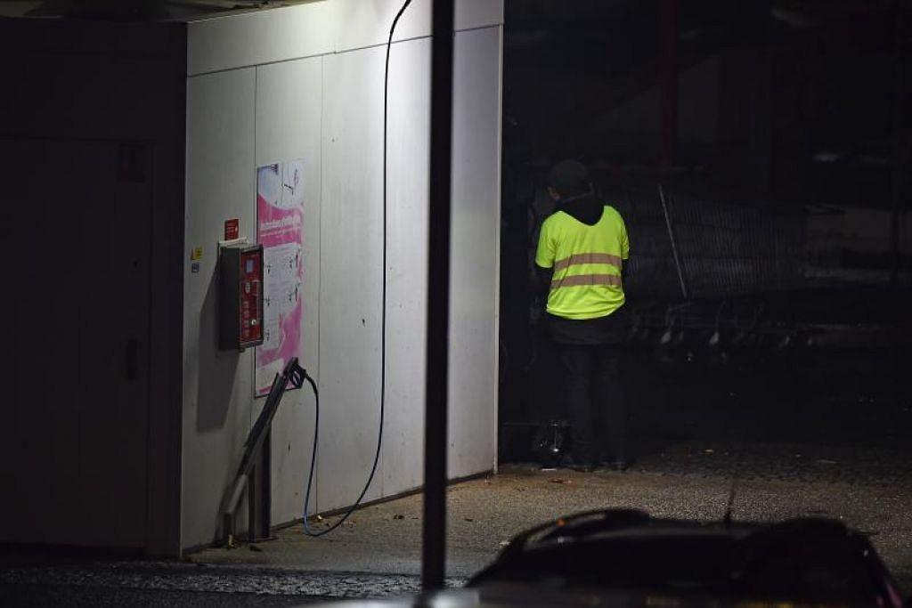 Caption: Lelaki yang memakai jaket kuning dan didakwa membawa bom tangan, yang mungkin gas pemedih mata, kelihatan di sebuah stesen minyak di Angers. Foto: AFP