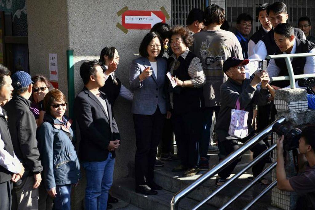 Presiden Taiwan Tsai Ing-wen (tengah) berbual dengan pengundi di sebuah pusat pengundian semasa pilihan raya tempatan di Zhongho, Taipei. - Foto AFP