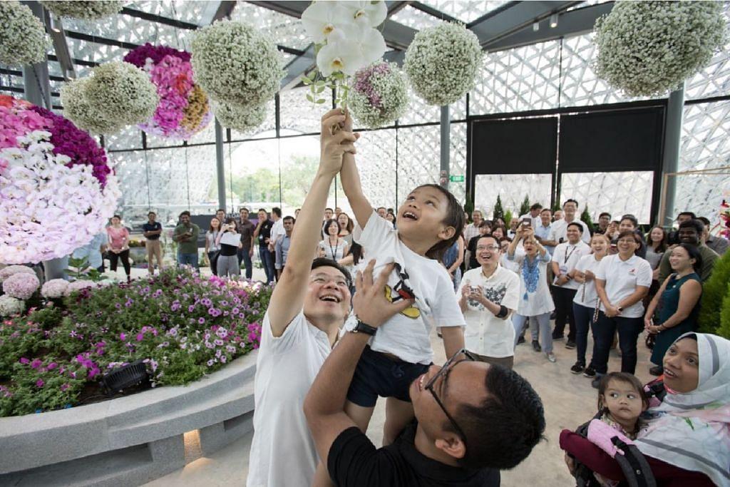 Menteri Pembangunan Negara, Encik Lawrence Wong (kiri) bersama Encik Khairi (berbaju hitam) dan anaknya (didukung) Hamza Muhammad Khairi menikmati keindahan semula jadi di pameran Floral Fantasy yang akan dibuka tahun depan. Foto: TAMAN DI PERSISIRAN