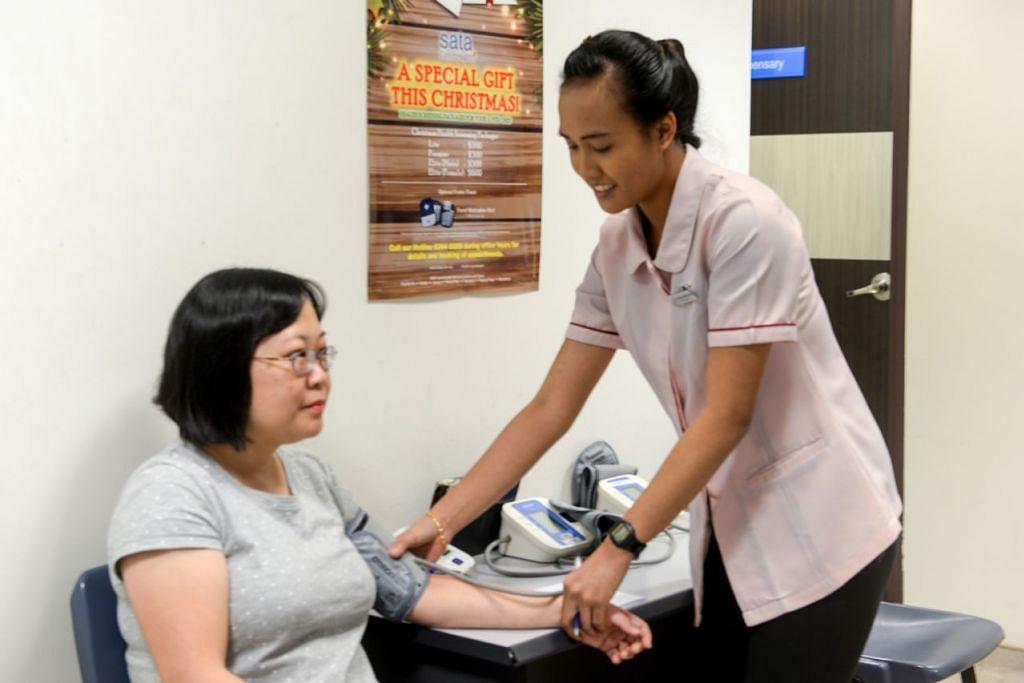 GEMBIRA MENJALANKAN TUGAS: Cik Nur Atikah Abdul Wahab (kanan) memeriksa tekanan darah seorang klien. Jururawat berdaftar itu menyertai Sata CommHealth pada awal tahun lalu. - Foto BM oleh PUTRI MARDHIYAH YAZID