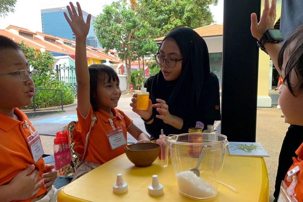 MINYAK ATAR: Kanak-kanak prasekolah berpeluang mencuba membuat minyak atar sendiri sambil dipantau oleh salah seorang pelajar Nafa (dua dari kanan).  - Foto BH oleh SITI AISYAH NORDIN