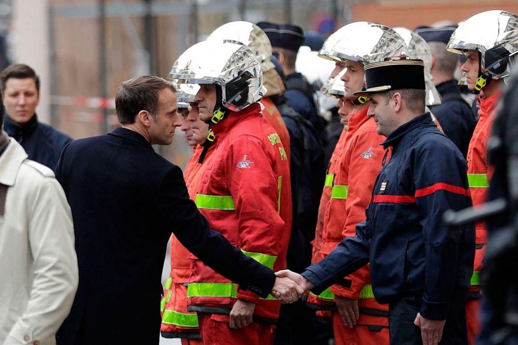 KUNJUNGI TEMPAT KEJADIAN: Presiden Perancis Emmanuel Macron (kiri) berjabat tangan dengan seorang anggota bomba semasa mengadakan lawatan di Paris menyusuli rusuhan oleh kumpulan antipemerintah yang membantah kenaikan cukai bahan bakar. - Foto AFP
