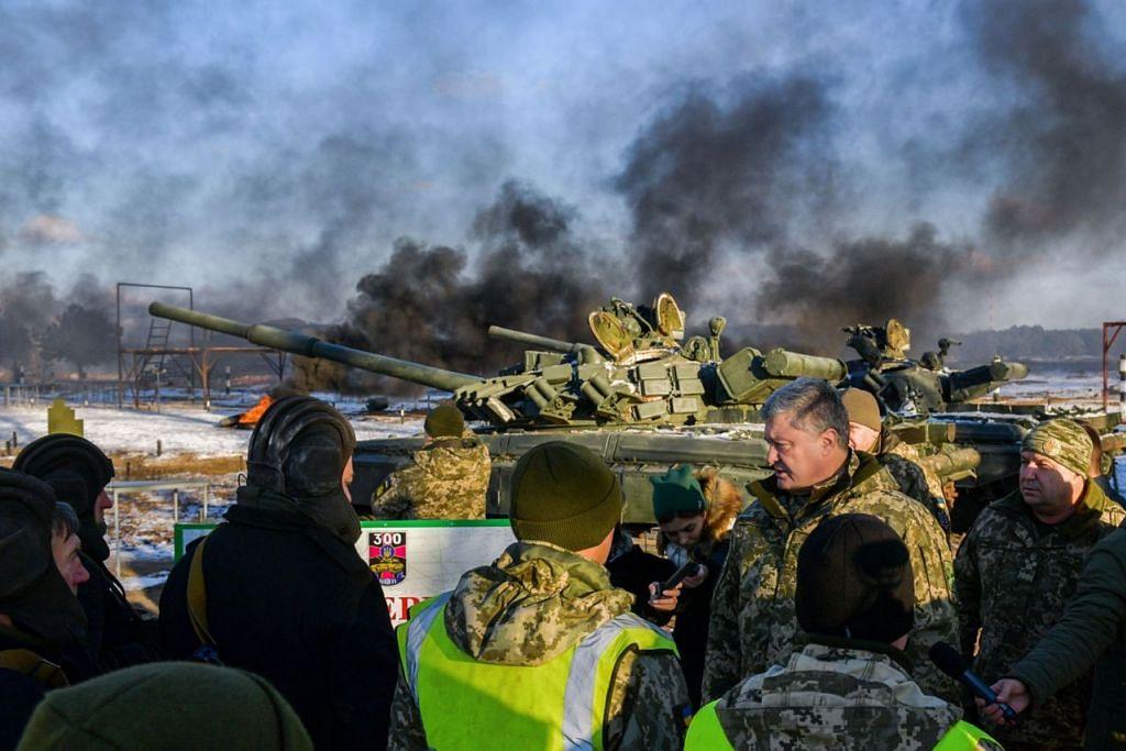 LATIHAN TENTERA: Presiden Petro Poroshenko (dua dari kanan) bercakap kepada askar tentera meriam semasa latihan berhampiran bandar Chernihiv di utara Ukraine pada 28 November lalu. Beliau mengenakan undang-undang tentera selama 30 hari di wilayah negara itu dekat sempadan dengan Russia, Laut Hitam dan Laut Azov setelah Moscow menawan dua kapal laut dan sebuah bot tunda Ukraine pada 25 November lalu. - Foto AFP