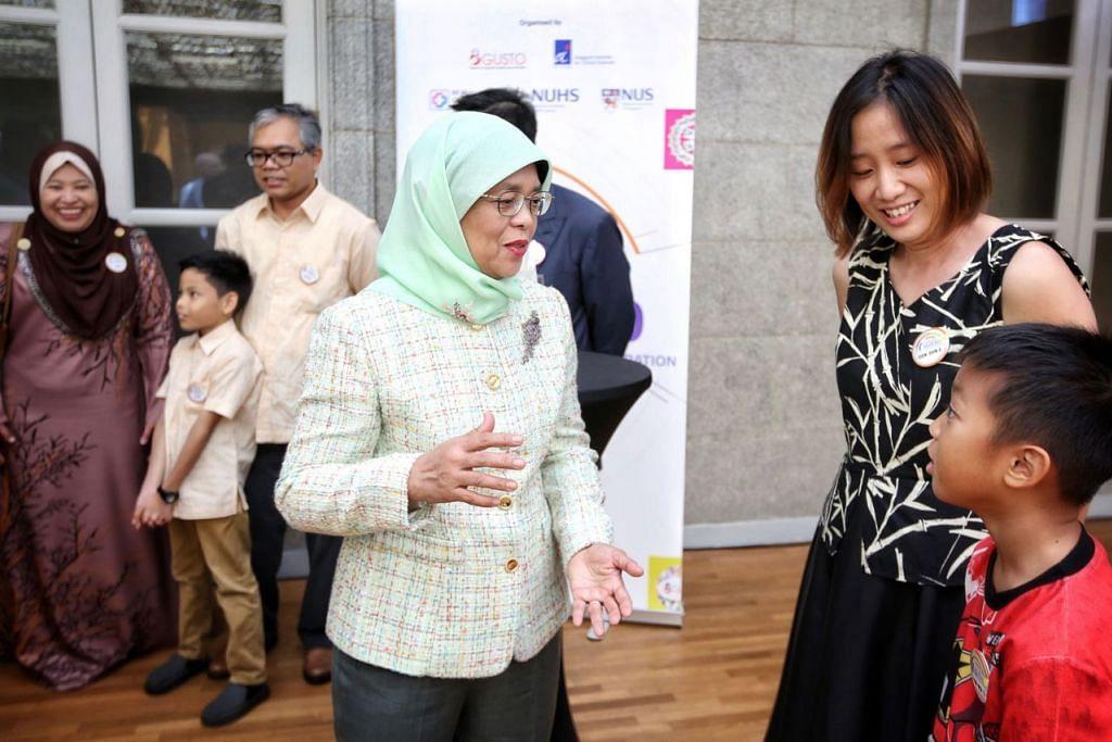 DEMI KEBAIKAN: Presiden Halimah Yacob berinteraksi dengan beberapa keluarga yang telah menyumbang kepada kajian yang dijalankan Gusto. - Foto SPH