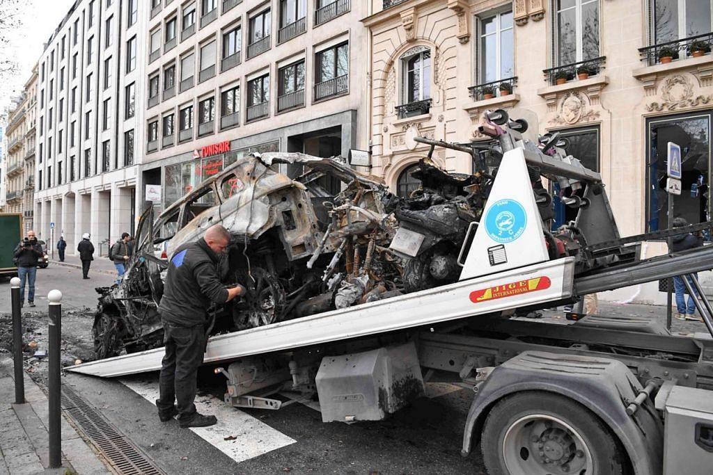 SISA-SISA RUSUHAN: Kereta yang hanya tinggal bangkai setelah dibakar semasa rusuhan penunjuk perasaan 'ves kuning' kelmarin dialihkan ke atas trak tunda semasa operasi pembersihan di Paris kelmarin. Penunjuk perasaan 'ves kuning' itu memprotes kos kehidupan yang kian meningkat di negara itu sambil menuntut peletakan jawatan Presiden Emmanuel Macron. - Foto AFP