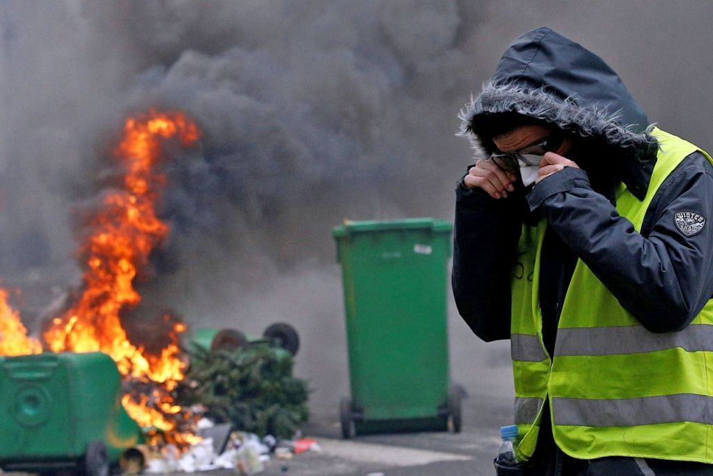 SISA-SISA RUSUHAN: Kereta yang hanya tinggal bangkai setelah dibakar semasa rusuhan penunjuk perasaan 'ves kuning' (gambar atas) kelmarin dialihkan ke atas trak tunda semasa operasi pembersihan di Paris kelmarin. Penunjuk perasaan 'ves kuning' itu memprotes kos kehidupan yang kian meningkat di negara itu sambil menuntut peletakan jawatan Presiden Emmanuel Macron. - Foto REUTERS