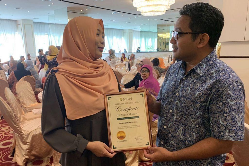 BERBESAR HATI: Encik Faiz menyampaikan sijil anugerah pencapaian kepada Cik Suryani setelah beliau berjaya menunjukkan semangat cekal dalam mempertingkat kehidupannya di Orchid Ballroom, The Central, semalam. - Foto BH oleh FAKHRURADZI ISMAIL