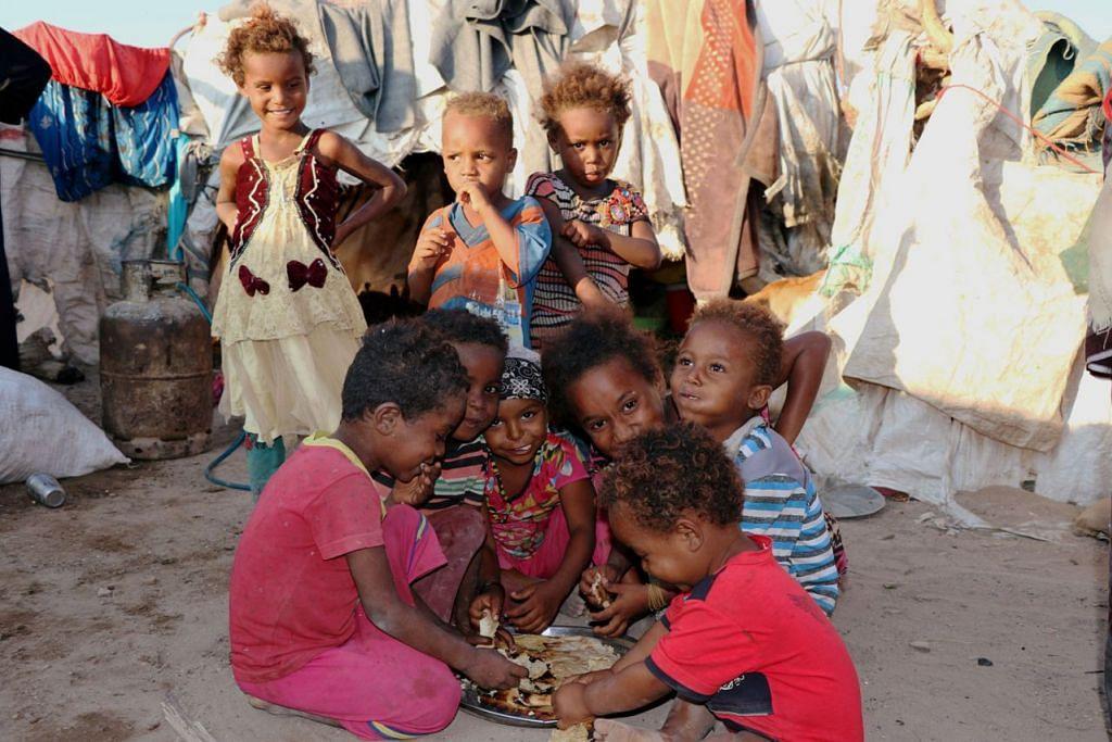 DI KANCAH KEBULURAN: Kanak-kanak berkongsi sedulang roti di sebuah khemah yang memberi perlindungan kepada rakyat Yaman yang terusir dari rumah mereka di Hodeida dekat Sanaa, ibu kota Yaman yang dikuasai pemberontak Houthi, pada 12 November. - Foto REUTERS