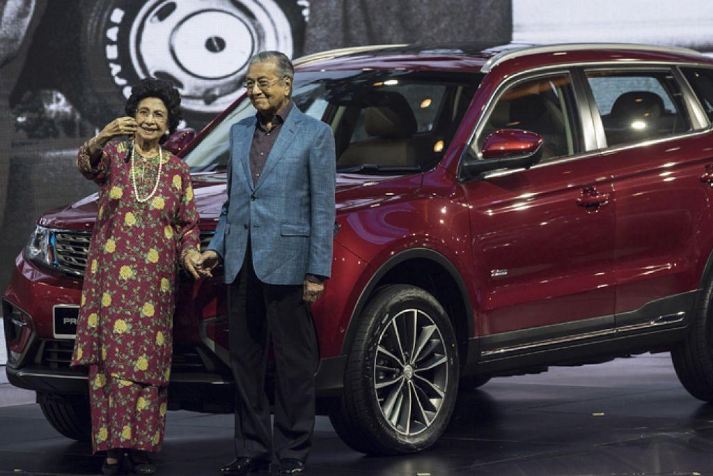 HARAP JADI KEBANGGAAN NEGARA: Dr Mahathir dan isteri Tun Dr Siti Hasmah bergambar di hadapan kereta jenis SUV, X70, yang dihasilkan menyusuli kerja sama Proton dan syarikat automotif dari China, Geely. - Foto EPA-EFE